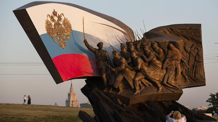 Tourists take pictures at a monument to the Heroes of the World War I as the sun sets over the scene on the eve of the day of the 100th anniversary of its beginning in Victory Park on Poklonnaya Hill in Moscow, Russia, Thursday, July 31, 2014. (AP Photo/Alexander Zemlianichenko)