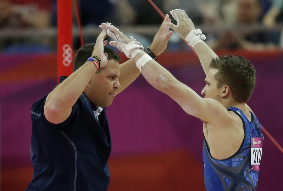 U.S. gymnast Jonathan Horton, right, celebrates with a team member after his performance on the horizontal bar during the Artistic Gymnastics men's qualification at the 2012 Summer Olympics, Saturday, July 28, 2012, in London. (AP Photo/Gregory Bull)