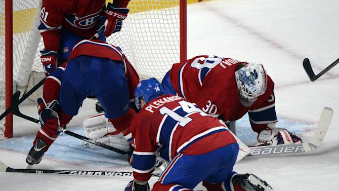 Montreal Canadiens goaltender Peter Budaj, right, reacts with fellow players Josh Gorges, left, and Tomas Plekanec after being scored on by the Ottawa Senators during the third period of Game 5 first round NHL hockey Stanley Cup playoff series in Montreal, Thursday, May 9, 2013. (AP Photo/The Canadian Press, Graham Hughes)