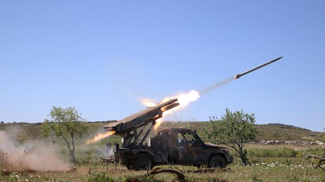 Rebel fighters from Ahrar al-Sham Islamic Movement fire grad rockets from Idlib countryside towards forces loyal to President Assad, who are stationed at Jureen town in al-Ghab plain in Hama countryside
