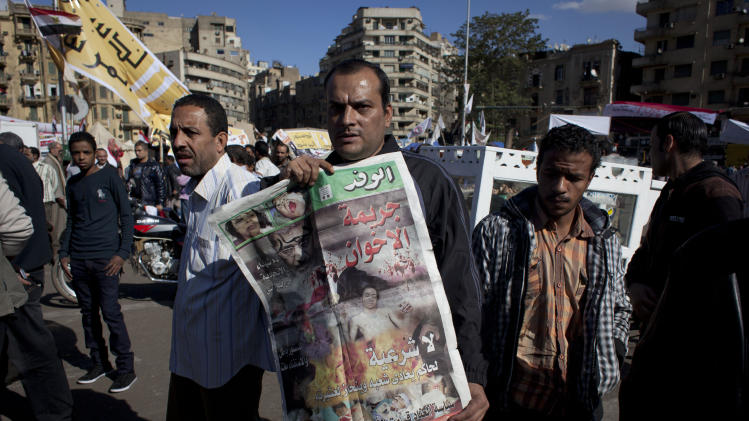 "An Egyptian protester carries a copy of Al Wafd newspaper front page that reads in Arabic ""the brotherhood's crime, no legitimacy for a governor who is against his people,"" during a protest against President Mohammed Morsi  near the presidential palace, in Cairo, Egypt, Friday, Dec. 7, 2012. Egypt's political crisis spiraled deeper into bitterness and recrimination Friday as thousands of Islamist backers of the president vowed vengeance at a funeral for men killed in bloody clashes earlier this week and large crowds of the president's opponents marched on his palace to increase pressure after he rejected their demands. (AP Photo/Nasser Nasser)"