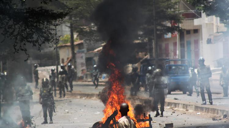 Security forces face off against opposition protestors from behind a burning street barricade, in Conakry, Guinea, Thursday, April 18, 2013. Security forces in Guinea arrested the opposition's spokesman and another leader Thursday after firing tear gas to disperse protesters who had planned a demonstration against the date set for upcoming legislative elections. The long-awaited vote has been a flashpoint for violent demonstrations over the last several months in this West African nation that long suffered under strongman rule. (AP Photo/Youssouf Bah)