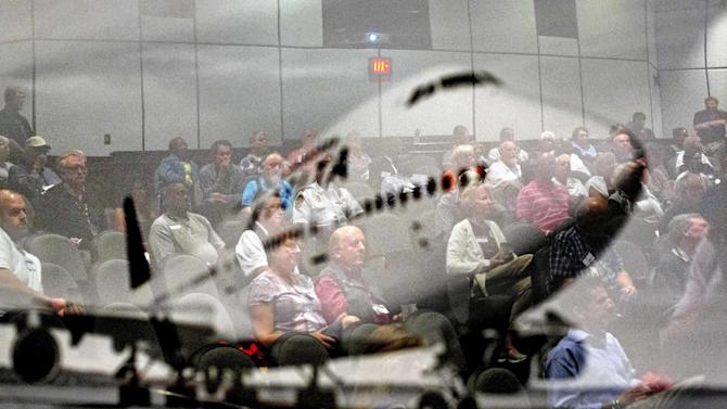 In this Friday, Sept. 20, 2013 photo, an image of a plane hangs on the wall as airport chaplains are reflected during a presentation at the International Association of Civil Aviation Chaplains' annual conference at Delta Air Lines' headquarters, in Atlanta. Airports are mini-cities with their own movie theaters, fire departments and shopping malls. Many also have chapels, which are staffed by a mix of 350 part- and full-time chaplains worldwide who are Catholic, Protestant and, to a lesser extent, Jewish, Muslim or Sikh. (AP Photo/David Goldman)