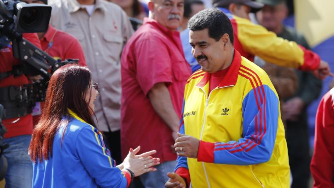 Venezuela's President Nicolas Maduro dances with first lady Cilia Flores during a rally to support the closing of the Colombian border, in Caracas, Venezuela, Friday, Aug. 28, 2015. President Maduro announced that he would extend the week-old partial closure of the border with Colombia to more cities and send additional troops to the area, doubling down on a policy has drawn rebuke by Colombian leaders. (AP Photo/Ariana Cubillos)