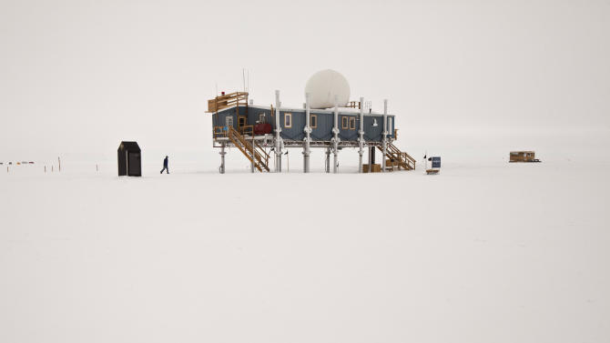 In this July 15, 2011 photo, in freezing temperatures, a researcher walks from an outhouse to the primary facility at Summit Station, a small U.S. National Science Foundation research center situated 10,500 feet above sea level, on top of the Greenland ice sheet. The primary facility is periodically jacked up on its support columns to stay above accumulating snow. Across Greenland's vast white landscape, small teams of researchers from around the world are searching for clues to the potential effects of global warming on Greenland's ice. (AP Photo/Brennan Linsley)