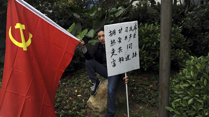 "A Communist loyalist holds a Chinese national flag and a banner which reads ""Protect Chairman Xi, Love the Communist Party, Walk together on the road to prosperity"" during a counter-protest  against supporters of the Southern Weekly newspaper outside the newspaper's headquarters in Guangzhou in south China's Guangdong province Tuesday Jan. 8, 2013.  Free-speech protesters in masks squared off against flag-waving communist loyalists in a southern Chinese city Tuesday as a dispute over censorship at a newspaper spilled into the broader population, with authorities shutting microblog accounts of supporters of the paper. (AP Photo) CHINA OUT"