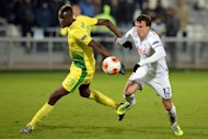 Tottenham defender Vlad Chiriches (R) challenges Anji Makhachkala forward Lacina Traoré during the UEFA Europa League Group K match in Ramenskoye outside Moscow on October 3, 2013