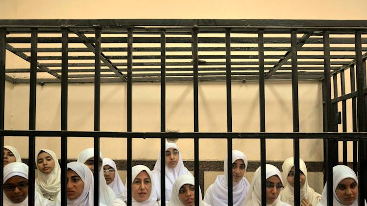 FILE - In this Nov. 27, 2013 file photo, Egyptian women supporters of ousted President Mohammed Morsi stand inside the defendants' cage in a courtroom facing six charges after holding an early morning protest on Oct. 31, in Alexandria, Egypt. Long kept in the background by conservatives, the women supporters of the Muslim Brotherhood have stepped ferociously into the front line of Islamist protests against Egypt's military and the interim government installed after Morsi's removal in a July 3 coup. In daily protests the past months, they have proven determined and ferocious. (AP Photo/Amira Mortada, El Shorouk Newspaper, File) EGYPT OUT