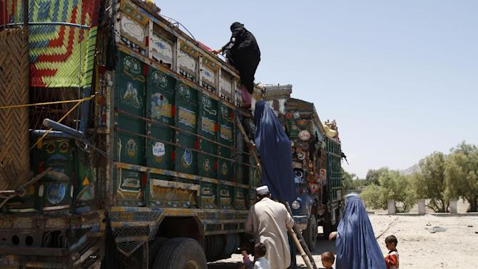 Afghan women climb onto a truck at the United Nations High Commissioner for Refugees (UNHCR) registration center on the outskirts of Jalalabad, east of Kabul, Afghanistan, on Wednesday, June 20, 2012, as they prepare to return to their home country after fleeing civil war and Taliban rule. World Refugee Day, a day initiated by the United Nations to raise awareness on the plight of refugees worldwide, is observed on June 20 every year. (AP Photo/Rahmat Gul)