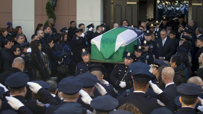 Police officers carry the casket of slain NYPD officer Ramos out of his funeral service at Christ Tabernacle Church to his final resting place in the Queens borough of New York