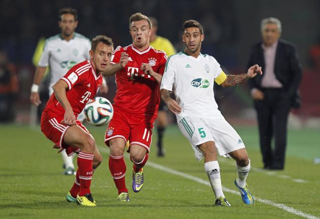 Mohsine Moutaouli of Morocco's Raja Casablanca fights for the ball with Xherdan Shaqiri (C) of Germany's Bayern Munich during their 2013 FIFA Club World Cup final soccer match at Marrakech sta