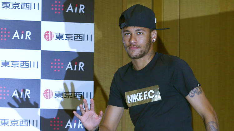 Brazil's soccer player Neymar waves to the media upon his arrival at a press conference at a hotel in Tokyo, Thursday, July 31, 2014
