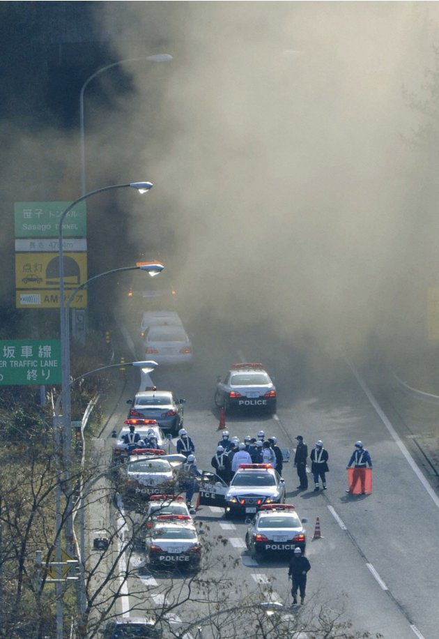 Smoke is seen from the Sasago Tunnel on the Chuo Expressway as Police officers gather in Koshu