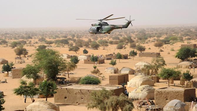A French army Puma helicopter flies over a village between Gao and Bourem, northern Mali, Sunday, Feb. 17, 2013. Mali's military detained eight Arab men last week in Timbuktu, raising fears of further reprisals against the region's Arab minority whose members are accused of having supported the al-Qaida-linked groups which overran northern Mali last year. (AP Photo /Pascal Guyot, Pool)