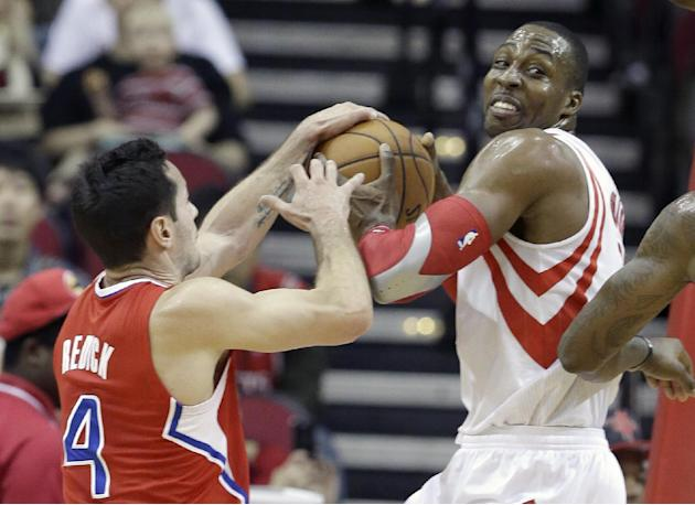 Los Angeles Clippers' J.J. Redick (4) and Houston Rockets' Dwight Howard, right, grapple for the ball in the first half of an NBA basketball game on Saturday, Nov. 9, 2013, in Houston