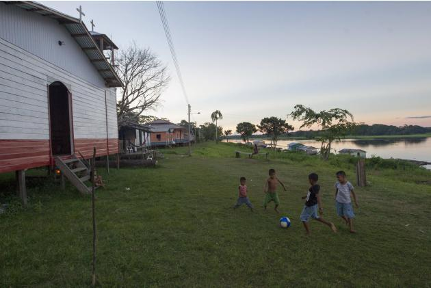 Children of the Sao Raimundo do Jaraua community play soccer along the edge of a tributary of the Solimoes river, one of the main tributaries of the Amazon