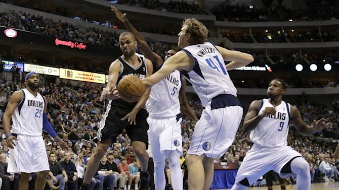 San Antonio Spurs' Tony Parker, second from left, of France, passes the ball from beneath the basket as Dallas Mavericks' Dirk Nowitzki (41), of Germany, defends in the second half of an NBA basketball game on Friday, Jan. 25, 2013, in Dallas. Mavericks' Vince Carter (25), Bernard James (5) and Jae Crowder (9) help on the play in the 113-107 Spurs win. (AP Photo/Tony Gutierrez)