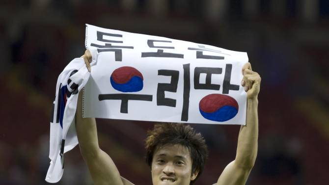 """FILE - This is a  Friday, Aug. 10, 2012 file photo of South Korea's Park Jong-woo as he holds up a banner reading """"Dokdo is our Territory,"""" referring to the largely uninhabited islets, midway between South Korea and Japan, after his team won their bronze medal men's soccer match against Japan, at the 2012 London Summer Olympics, at the Millennium Stadium in Cardiff, Wales.  An official  Tuesday Feb. 12, 2013, familiar with the decision says South Korea's Park Jong-woo who displayed a political banner after a match at the London Olympics will receive his bronze medal. (AP Photo/Jon Super, File)"""