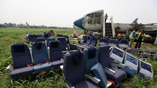 Seats removed from the fuselage of an abandoned aircraft are piled up at Murtala Muhammed International Airport in Lagos, Nigeria, Thursday, Jan. 31, 2013. Nigerian aviation officials have begun trying to dismantle and remove the hulks of abandoned airplanes from airports around the country. Officials say there are least 65 abandoned planes at the country's airports, with at least 13 at Lagos' international airport. (AP Photo/Jon Gambrell)
