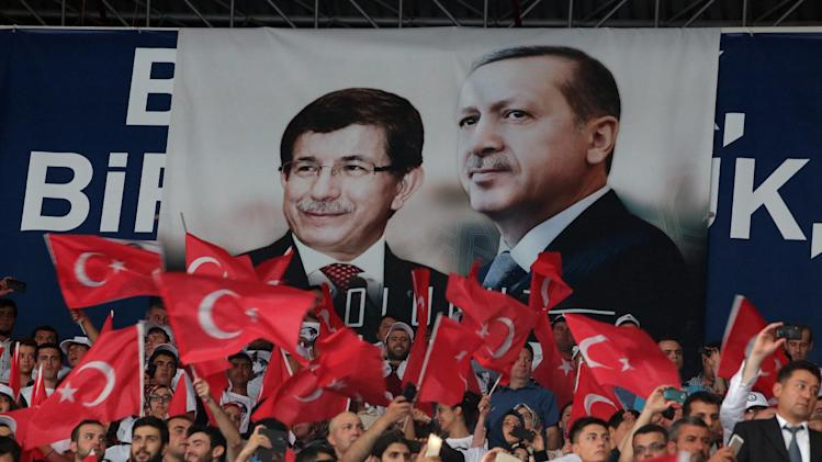 Supporers wave flags in front of a poster of President-elect Recep Tayyip Erdogan, right, and Foreign Minister Ahmet Davutoglu in Ankara, Turkey, Wednesday, Aug. 27, 2014. Turkey's ruling party convened on Wednesday to confirm Foreign Minister Ahmet Davutoglu as its new chairman and prime minister-designate, to replace Recep Tayyip Erdogan as he becomes president — a position he has pledged to transform from a ceremonial post to one of real power. (AP Photo/Burhan Ozbilici)