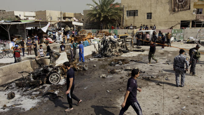 Iraqis inspect the scene of a car bomb attack in the Ameen neighborhood in eastern Baghdad, Iraq, Sunday, Feb. 17, 2013. A series of car bombs exploded within minutes of each other as Iraqis were out shopping in and around Baghdad on Sunday, killing and wounding scores of people, police said. (AP Photo/ Khalid Mohammed)
