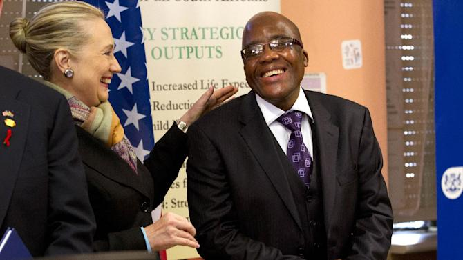 Secretary of State Hillary Rodham Clinton talks with South Africa's Health Minister Aaron Motsoaledi, after attending a PEPFAR (U.S. President's Emergency Plan for AIDS Relief) Transition Signing, Wednesday, Aug. 8, 2012, at the Delft South Clinic in Delft South, a suburb of Cape Town, South Africa. (AP Photo/Jacquelyn Martin, Pool)