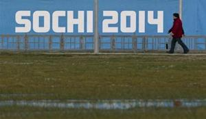People walk past a banner near venues in the Olympic Park in Adler near Sochi