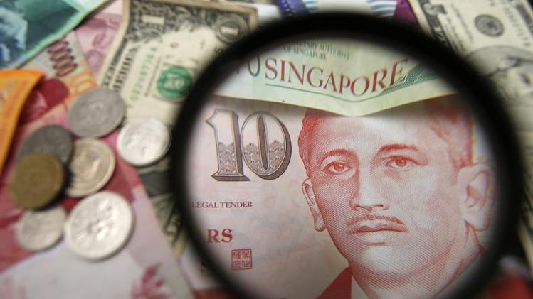 Photo illustration of bank notes and coins of various currencies including the Singapore dollar.
