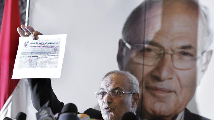"Egyptian presidential candidate Ahmed Shafiq holds a clipping from an Arabic newspaper with a headline that reads, ""The Muslim Brotherhood--not suited for presidency or government,"" during a press conference in Cairo, Egypt, Sunday, June 3, 2012. Shafiq, the last prime minister of deposed President Hosni Mubarak, will face the Muslim Brotherhood candidate Mohammed Morsi in a run-off on June 16-17. (AP Photo/Amr Nabil)"