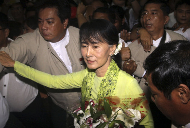 In this Sunday, Sept. 16, 2012 photo, Myanmar opposition Leader Aung San Suu Kyi, center, arrives at Yangon International airport, Myanmar,