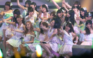 FILE - In this June 6, 2012 file photo, Japans all-girl pop idol group AKB48 members perform during the annual AKB48 popularity poll in Tokyo. More than 60 girls and young women, split into four teams, make up what is arguably Japan&#39;s most popular pop group. It performs almost every day, has spawned affiliate groups across the country and has recently given rise to sister mega-groups in China and Indonesia. (AP Photo/Shizuo Kambayashi, File)