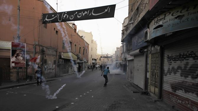 Protesters, demonstrating for Salman, run for cover as riot-police fire tear gas canisters in a street in the village of Bilad Al Qadeem