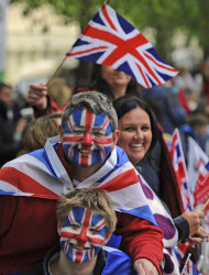 Spectators wait for Britain's Queen Elizabeth II and the royal family to pass along The Mall for a service of thanksgiving at St Paul's Cathedral as part of the Diamond Jubilee celebrations Tuesday June 5, 2012. Queen Elizabeth II will make a rare address to the nation at the conclusion of festivities marking her 60 years on the throne. (AP Photo/Tom Hevezi)