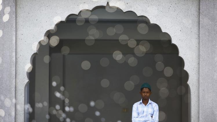 A Nepalese Muslim waits to offer prayer during Eid al-Fitr celebrations at a mosque in Kathmandu