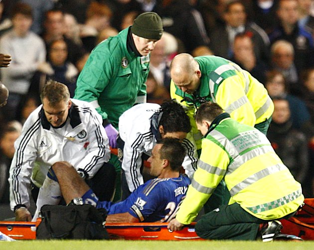 John Terry, centre, was stretchered off after a collision with Luis Suarez