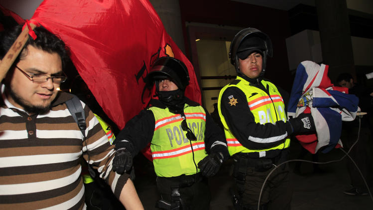 A police officer, right, carries a British flag, taken from demonstrators, after a protest outside the United Kingdom's embassy in Quito, Ecuador, Wednesday, Aug. 15, 2012. Ecuador accused Britain on Wednesday of threatening to storm its London embassy to arrest Julian Assange after the U.K. issued a stern warning to the South American nation ahead of its decision on an asylum bid by the WikiLeaks founder. People protested against the alleged threat. (AP Photo/Dolores Ochoa)