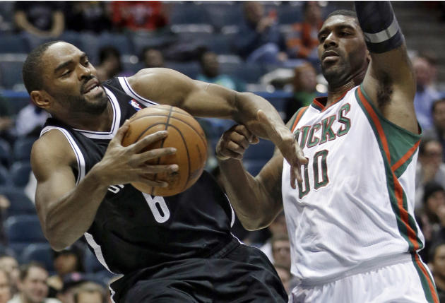 Brooklyn Nets' Alan Anderson is fouled as he tries to drive past Milwaukee Bucks' O.J. Mayo during the first half of an NBA basketball game Saturday, Dec. 7, 2013, in Milwaukee