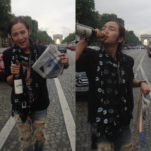 Jang Geun Suk walking on avenue des Champs-Élysées with a wine and a newspaper