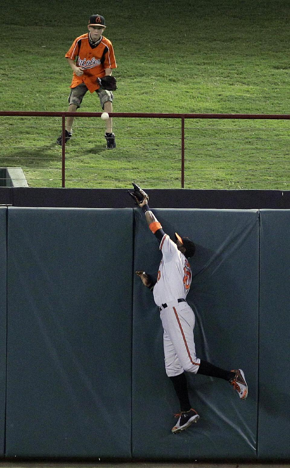 Baltimore Orioles center fielder Adam Jones (10) cannot reach the solo home run hit by Texas Rangers Adrian Beltre as a young fan, top, waits for the ball during the fourth inning of a baseball game on Wednesday, Aug. 22, 2012, in Arlington, Texas. (AP Photo/LM Otero)