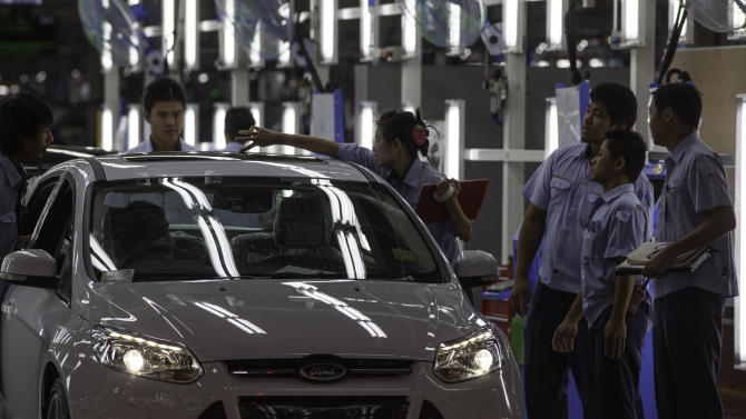 Thai Ford Manufacturing employees look on Friday, Aug. 31, 2012, as a new Ford Focus is checked out at the Ford Manufacturing plant in Rayong, Thailand.  Ford held a ceremony Friday to announce the 350 millionth globally produced Ford Focus. (AP Photo/str)
