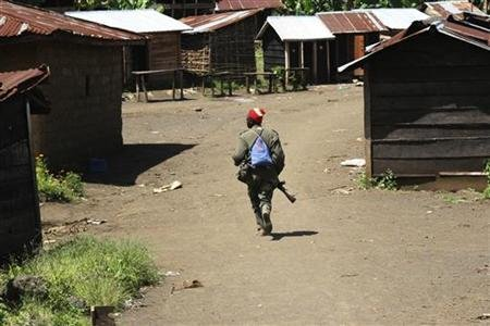 A government soldier runs through the deserted town of Rutsiro near the front line in eastern Congo