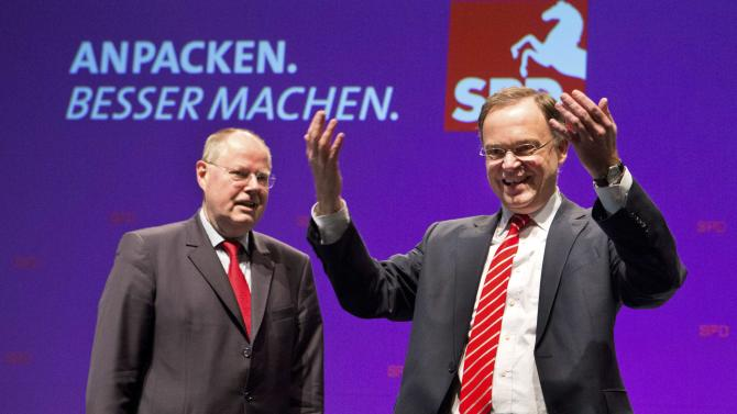 FILE - In this Jan 4, 2013 file photo, Stephan Weil, right, Social Democratic top candidate for the state elections in Lower Saxony, and Peer Steinbrueck, Chancellor Angela Merkel's challenger in the upcoming general elections, during a election campaign rally in Emden, northern Germany. Merkel is riding high in polls as she seeks a third term at the head of Europe's biggest economy. But a major state election this weekend may lift her center-left rivals' hopes of defying the odds and ousting her as Germany's leader.  The Sunday balloting is one of only two significant electoral tests before national parliamentary elections. Recent polls in Lower Saxony show the Social Democrats and Greens neck-and-neck with Merkel's party and the Free Democrats. (AP Photo/dapd, Joerg Sarbach, File)