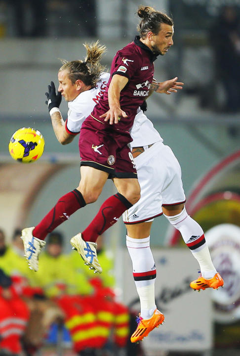 AC Milan's Philippe Mexes, right, and Livorno's Sergio Paulinho, of Brazil, vie for the ball during a Serie A soccer match between Livorno and AC Milan in Leghorn, Italy, Saturday, Dec. 7, 201