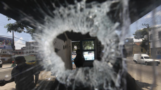 A bullet hole pierces the window of a small police station in the Del Castilho neighborhood in Rio de Janeiro, Brazil, Tuesday Nov. 23, 2010.  Rio's entire military police force was ordered into the streets after more gang attacks ended with two motorists shot dead, cars burned and mass robberies on highways. (AP Photo/Silvia Izquierdo)