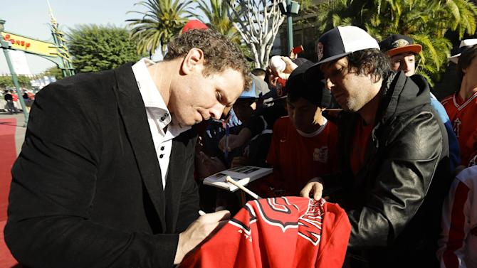 Free-agent outfielder Josh Hamilton, left, signs a autograph for a fan on his way into a news conference at the ESPN Zone restaurant in Anaheim, Calif., Saturday, Dec. 15, 2012. Hamilton, formerly of the Texas Rangers, joins the Los Angeles Angels MLB baseball team after signing a $125 million, five-year contract. (AP Photo/Chris Carlson)