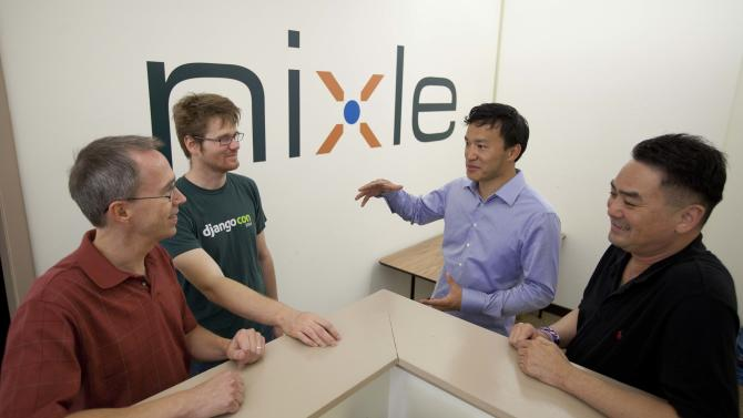 In this photo taken Tuesday, Aug. 7, 2012 from left, Joe Rantala, software developer, Patrick Boyd, vice-president of engineering, Eric Liu, CEO and Charles Choy, director of quality assurance gather for a discussion at the offices of Nixel in San Francisco. Across the country, law enforcement agencies have added a new form of social media to their arsenal of crime fighting tools. Thousands of cash-strapped police departments are now heavily relying on the notification service Nixle to provide residents with real-time alerts on crimes in progress, traffic messes and missing children. (AP Photo/Eric Risberg)
