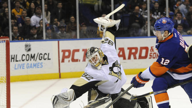 New York Islanders' Josh Bailey (12) shoots the puck past Pittsburgh Penguins goalie Tomas Vokoun (92) to score in the second period of an NHL hockey game on Friday, March 22, 2013 at Nassau Coliseum in Uniondale, N.Y. (AP Photo/Kathy Kmonicek)