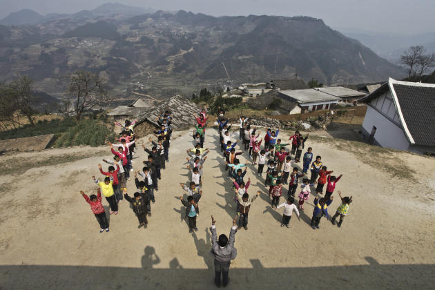 Xu Liangfan, 37, and students exercise at the playground of Banpo Primary School in Shengji county
