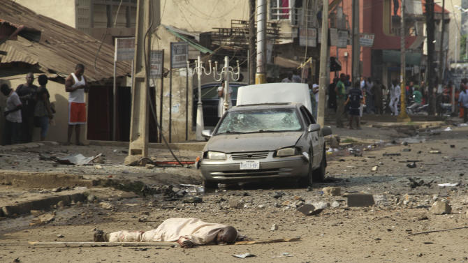 A body is seen at the site of a bomb explosion at a road in Kaduna, Nigeria on Sunday, April 8, 2012. An explosion struck the city of Kaduna in central Nigeria  on Sunday  that has seen hundreds killed in religious and ethnic violence in recent years, causing unknown injuries as diplomats had warned of possible terrorist attacks over the Easter holiday, police said.(AP Photos/Emma Kayode)