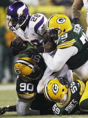 Minnesota Vikings running back Adrian Peterson (28) is taken down by Green Bay Packers nose tackle B.J. Raji (90), inside linebacker Brad Jones (59) and defensive end Ryan Pickett (79) during the first half of an NFL wild card playoff football game Saturday, Jan. 5, 2013, in Green Bay, Wis. (AP Photo/Kiichiro Sato)